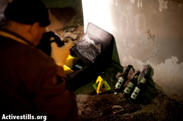 Forensic workers take pictures of unused Molotov cocktails